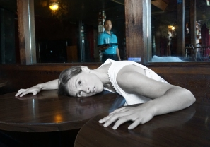 The bartender (Enormvs Muñoz, above) knows more Maggie (Adrian Deane) that he is able to reveal. Photo by Shannon Davis